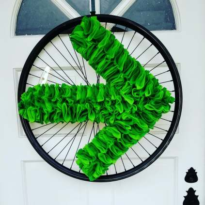 Light and dark green felt Pelotonia arrow  with black bike wheel rim wreath on white door.