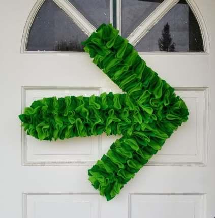 Light and dark green felt Pelotonia arrow wreath on white door.